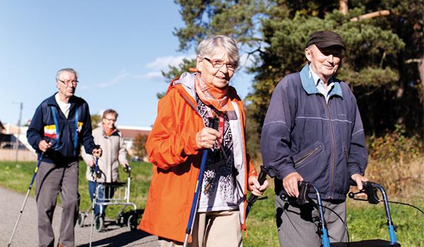 Neljä ihmistä sauvakävelemässä keväisenä päivänä.