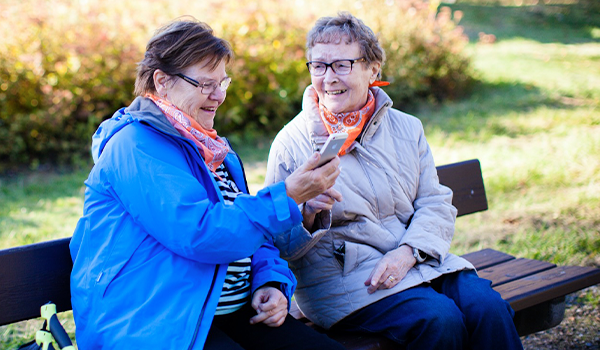 Kaksi hymyilevää naista istuu puistonpenkillä, toinen katsoo puhelintaan.